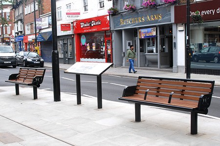 Two new benches on the pavement facing away from the traffic with an information board (not legible)