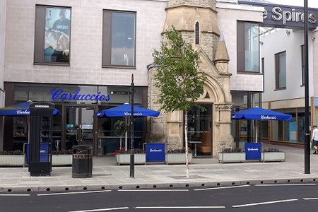 cafe with outdoor seating, blue parasols and the remains of part of a church spire