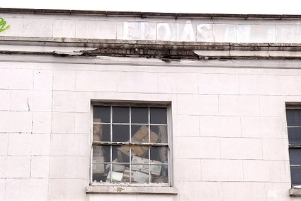 window with boxes piled up inside and a disintegrating parapet above it