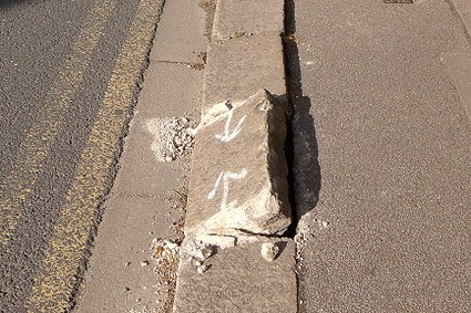 close up of a classic wide Barnet kerbstone dislodged by being driven on