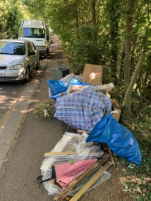 fly-tipped rubbish in blue plastic sacks