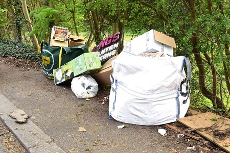 a pile of rubbish at the side of the road, with cardboard boxes and a large bag as used for building materials