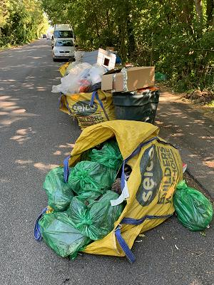 fly-tipped rubbish in yellow builders merchant bags