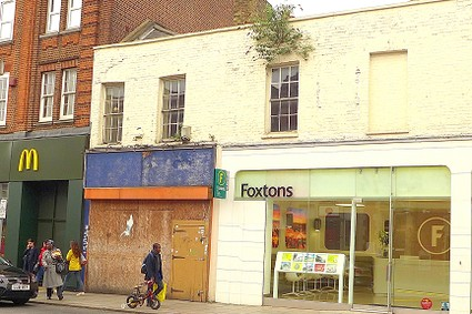 scruffy shop front with a small tree growing out of it