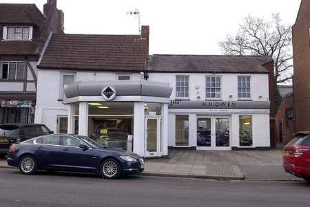 old house with car showroom extension on the front, white painted