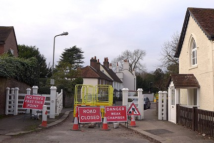 narrow road closed off with signs 'no HGVs past this point', 'road closed' and 'danger weak chamber'