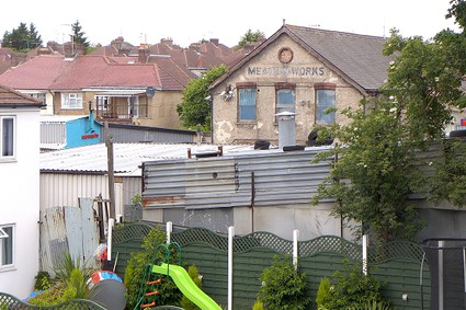 old industrial building, corrugated iron roof and childrens slide in foreground