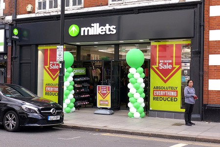 Millets shop with green and white balloons outside
