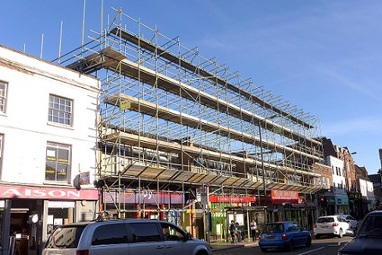 row of shops with tall scaffolding in front and over