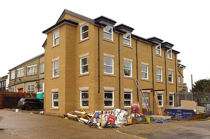 three storey block of flats nearing completion, yellow brick