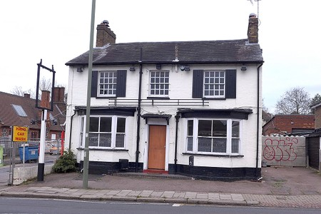 closed pub, two storey whitewashed house with shutters and slate roof